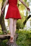Eine Blondine in einem roten Kleid geht in den Park Stockbild