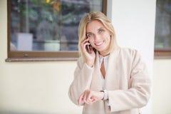 Eine Blondine mit einer Armbanduhr spricht am Telefon und lächelt lizenzfreie stockfotografie