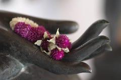 Eine Blumengirlande in der Hand von Buddha Stockbild