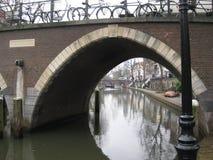 Eine Bogenbrücke über einem alten Kanal in Utrecht, die Niederlande lizenzfreie stockfotografie