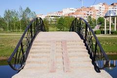 Eine Brücke über dem Fluss im Park Stockfotografie