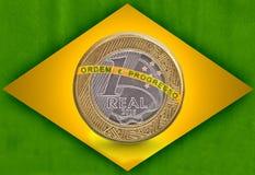 Eine brasilianische wirkliche Flagge mit einer ein wirklichen Münze nach innen Stockfotos