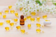 Eine braune Flasche ml mit neroli ätherischen Ölen, eine Pipette, Goldkapseln der natürlichen Kosmetik und Blumen blühen auf Stockbild