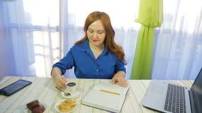 Eine braunhaarige Frau in einem Café an einem Tisch schreibt in ein Tagebuch und in einen Getränkkaffee stock video