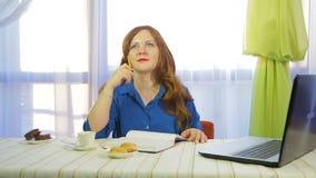 Eine braunhaarige Frau in einem Caf? am Arbeits- und Getr?nkkaffee einer Tabelle stock footage