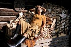 Eine braunhaarige Frau liegt auf Klotz und Holz auf dem Hintergrund eines Holzhauses, Lizenzfreies Stockbild