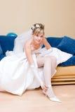 Eine Braut, die auf einen Schuh sich setzt Stockbild