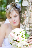Eine Braut mit einem Blumenblumenstrauß durch den Baum Stockfotos