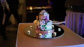 Eine Braut und ein Bräutigam schneidet ihre Hochzeitstorte stock footage