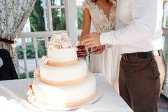 Eine Braut und ein Bräutigam schneidet ihre mehrstufige weiße Hochzeitstorte stockbilder