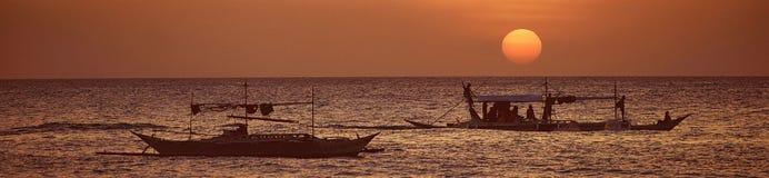 Eine breite Ansicht des Meeres und der Boote bei einem Sonnenuntergang Lizenzfreies Stockfoto
