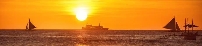Eine breite Ansicht des Meeres und des Bootes bei einem Sonnenuntergang Lizenzfreies Stockbild