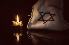Eine brennende Kerze nahe bei dem Davidsstern Lizenzfreie Stockfotos