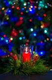 Eine brennende rote Kerze mitten in dem Weihnachtskranz gegen den dunklen Hintergrund auf dem Weihnachtsbaum stockfoto