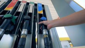Eine Brennstoffpistole wird von einer Gaspumpe herausgenommen Benzin, Gas, Brennstoff, Erdölkonzept stock footage