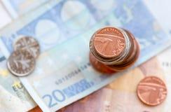 Eine britische Pennymünze und Eurobanknoten Stockbilder
