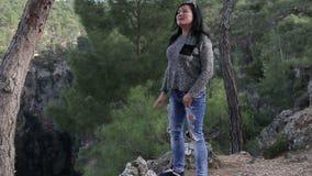 Eine Brunettefrau, die auf dem Abgrund der aufwerfenden und lächelnden Schlucht steht stock footage