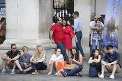 Eine bunte Menge, die auf der Pflasterung für Rest sitzt Lizenzfreies Stockfoto