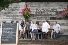 Eine bunte Menge sitzt außerhalb der Kneipe, trinkt Bier, spricht mit Freunden Stockfotos
