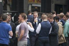 Eine bunte Menge sitzt außerhalb der Kneipe, trinkt Bier, spricht mit Freunden Gemüse im Kasten Lizenzfreie Stockfotografie