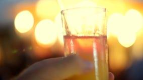 Eine Cocktailparty, ein Getränk mit Eis in einem Glas mit einem Rohr, in den Strahlen von Laibungen, die Lampen, flackernd beleuc stock video