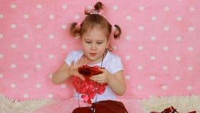Eine Dame des kleinen Mädchens in der Sonnenbrille in Form der Herzen Lustiges Kind Rosa Hintergrund zauber Art und Weise Fashion stock video