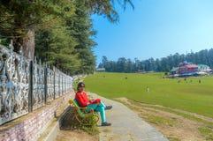 Eine Dame, die auf einem Golfplatz sitzt und sich entspannt lizenzfreie stockfotografie