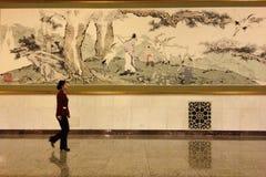 Eine Dame, die durch eine chinesische Malerei im Großen Hall von Leuten in Peking überschreitet Stockbild