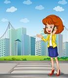 Eine Dame mit einem Mobiltelefon, das am Fußgängerweg steht Lizenzfreies Stockfoto