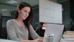 Eine Dame Sitting im Büro, das an einem Laptop arbeitet stockfotos
