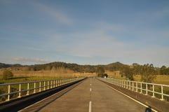 Eine Datenbahnstraßenbrücke läuft zu den grünen Hügeln spitz zu Stockfoto
