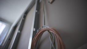 Eine Detailansicht von den grauen und orange elektrischen Kabeln, die innerhalb einer Wandeinschließung in den Spiralen und in de stock footage