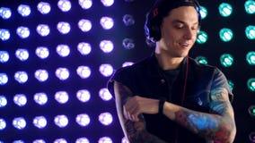 Eine Discoplatte mit bunten Lichtern hinter einem DJ stock footage