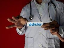Eine Doktorstellung, halten den Diabetespapiertext auf rotem Hintergrund Medizinisches und Gesundheitswesenkonzept stockbilder
