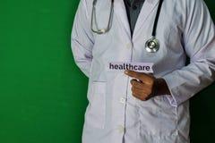 Eine Doktorstellung, halten den Gesundheitswesenpapiertext auf grünem Hintergrund Medizinisches und Gesundheitswesenkonzept stockfotografie