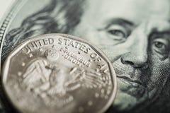 Eine Dollarmünze auf dem hundert Dollarschein Lizenzfreie Stockbilder