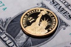 Eine Dollarmünze - das Freiheitsstatue - auf einer Dollarbanknote Stockbilder