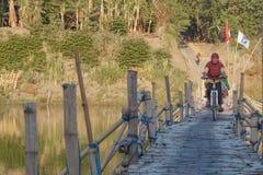 Eine Dorfbewohnerfunktion als Kaufmann im traditionellen Markt, der die Brücke des Bambusses kreuzt lizenzfreies stockfoto