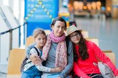 Eine dreiköpfige Familie, die in einem Erholungsgebiet am Flughafen sitzt stockbilder