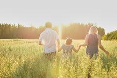 Eine dreiköpfige Familie mit einer Tochter geht über das Feld in Richtung zur untergehenden Sonne, Händchenhalten unschärfe Hinte stockfotografie