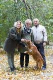 Eine dreiköpfige Familie zieht einen Hund ein lizenzfreie stockbilder