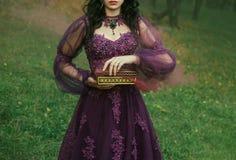 Eine dunkelhaarige junge Dame hält in ihren Händen offenes der Büchse der Pandora, den roten kastanienbraunen starken Nebel des Ü stockfotografie