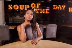 Eine durchdachte afroe-amerikanisch Frau in einem Café lizenzfreies stockfoto