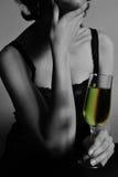 Eine durchdachte Frau hält Glas mit Champagner an Stockbilder
