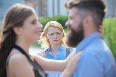 Eine eifersüchtige Freundin Unglückliches Mädchengefühl eifersüchtig Bärtiger Mann, der seine Freundin mit einer anderen Frau bet stockbilder