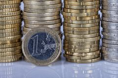 Eine ein-Euro-Münze vor vielen mehr Münzen gestapelt in Spalten O stockbilder