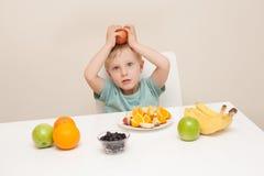 Eine Einfassung des kleinen Jungen durch Frucht.  Das Kind wird wieder fotografiert Lizenzfreie Stockbilder