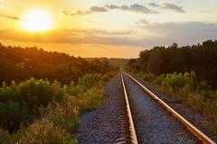 Eine eingleisige Eisenbahn mitten in dem Waldsonnenuntergang, hinter Lizenzfreie Stockbilder