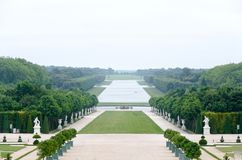 Eine einsame Ansicht von Versailles-Park, Frankreich Die geometrische Kombination von grünen Bäumen, von Grasbereichen und von we stockfotografie