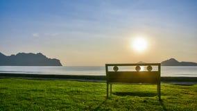 Eine einsame Bank auf grünem Gras nahe der Küste an AO Manao Lizenzfreie Stockbilder
